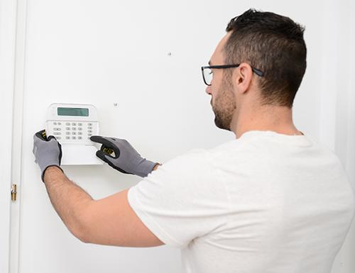 man installing security panel