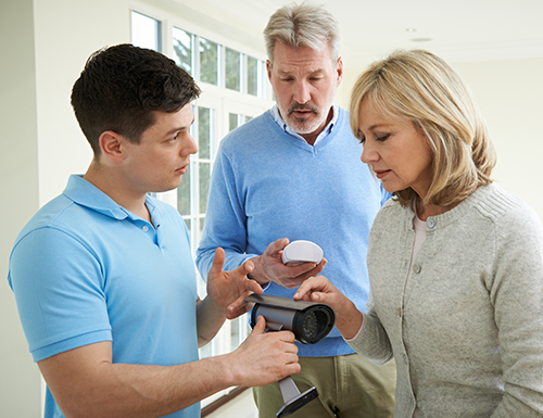 salesman showing a couple different camera options for their home security